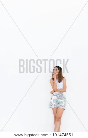 an asian girl with white undershirt and shorts is think on the white background with some space for text