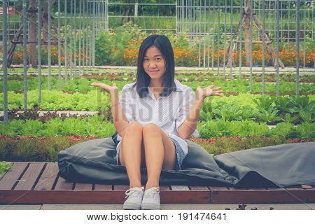 Portrait Asian woman sitting on black pillow and wooden terrace in the garden, smiling and holding open hand sideways with green natural background. (Autumn filter effect)