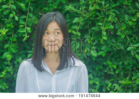 Shoot photo Asian woman portrait wear white shirt, thinking and looking sideways with green tree background. (Autumn filter effect)