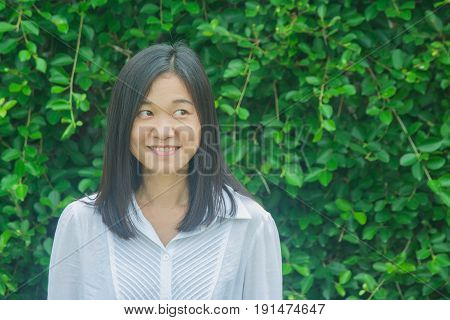 Shoot photo Asian woman portrait wear white shirt, smiling and looking sideways with green tree background. (Autumn filter effect)