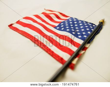 Close-up detail of an old handheld waving American flag in reverse used in multiple national holidays. USA and freedom concept.