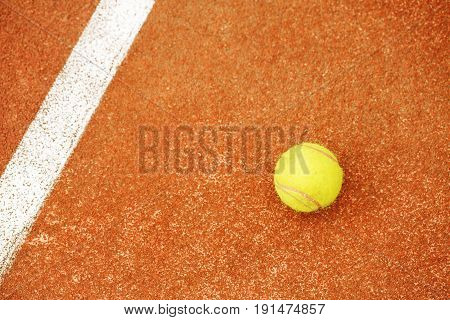 One yellow tennis ball lies on the tennis court. The concept of sport.
