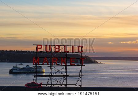 SEATTLE USA - MARCH 25 2016: Quiet sunset over Puget Sound on March 25 2016 in Seattle USA. Red fluorescent sign of Seattle famous Public Market and horizon over the land.