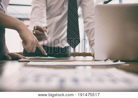 Businesswoman Working With Businessman. Two Business People Discussing Document And Idea At Meeting.