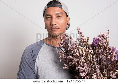 Asian Young Man Wearing Casual T-shirt And Cap Holding A Bouquet Of Purple Flower Standing Against A