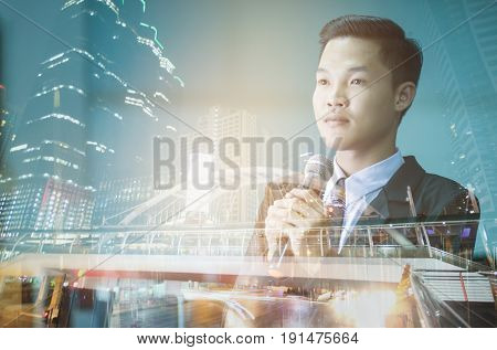 Double exposure of success businessman speech with microphone on traffic beautiful night view in business city centre : investment and business concept