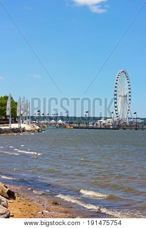 OXON HILL MARYLAND USA - JULY 4 2014: The National Harbor coastline and pier with Ferris on July 4 2014 in National Harbor Maryland USA.