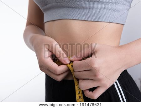 Sporty Fitness Woman Use Measuring Tape To Measure The Waist. Young Girl Taking Measurements Of Her
