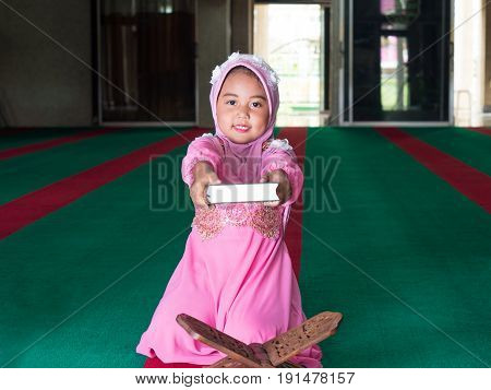 happy muslim girl with full hijab in pink dress asian traditional style dress reading the holy book Quran.