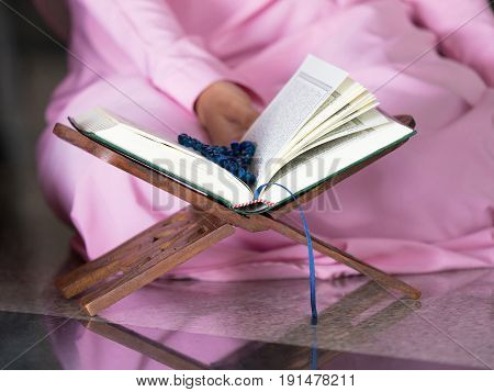 happy muslim woman with full hijab in pink dress asian traditional style dress reading the holy Quran book
