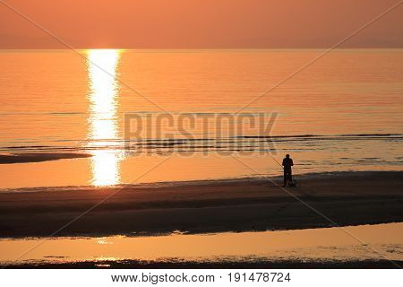 Beautiful sunset beach and sea landscape with fisher