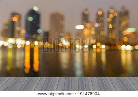 Opening wooden floor City office building and reflection blurred bokeh light night view abstract background