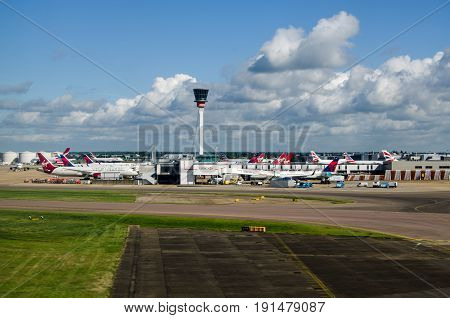 LONDON UK - JUNE 3 2017: View from above the ground of the main control tower at London Heathrow Airport on a sunny morning in early summer. Aircraft from many international airlines use the base including American Airlines Delta Airlines Virgin Atlantic