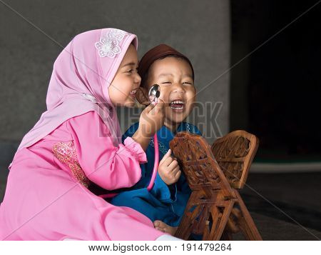 happy muslim girl with full hijab in pink dress asian traditonal style dress playing with her brother inside mosque.