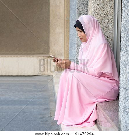happy muslim woman with full hijab in pink dress asian traditional style dress using smart phone