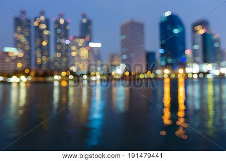 Blurred bokeh blue twilight sky office building with reflection light night view abstract background