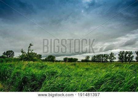 Green meadow with  - dark storm clouds