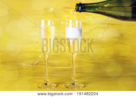 Champagne being poured into glasses on a blurred golden background with shining lights, with a place for text