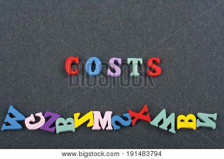 costs word on black board background composed from colorful abc alphabet block wooden letters, copy space for ad text. Learning english concept
