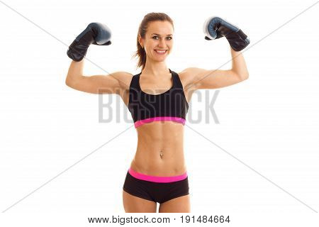 strong athletic girl in boxing gloves strained muscles in her arms and smiling isolated on white background