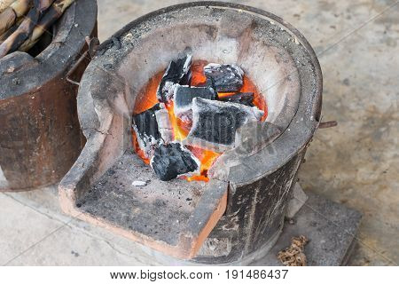 charcoal burning clay stove in a rustic wooden house.