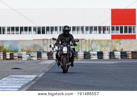 A motorcycle racer in black uniform takes a practice run on a sports track