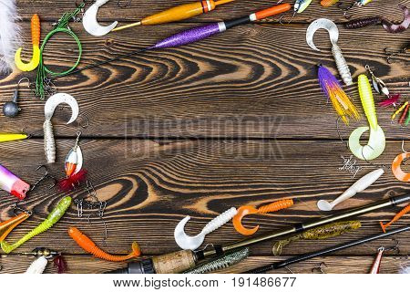 Sankt-Petersburg Russia June 16 2017: Fishing rod tackles and fishing baits reel on wooden board background