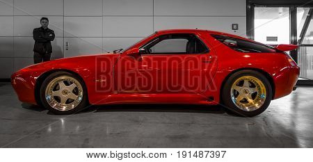 STUTTGART GERMANY - MARCH 02 2017: Sports car Porsche 928 S4 Strosek Design. A colored car on a black and white background. Europe's greatest classic car exhibition