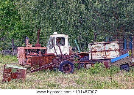 Old rusty tractor with a trailer and scrap metal in a field near trees