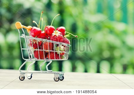 Fruity shopping cart full of strawberries cherries. Farmers harvest on greenery landscape background, Shallow depth field, selective focus, copy space.