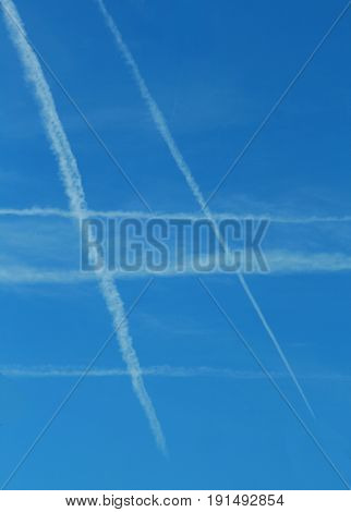 contrails on clear sky building a checked pattern