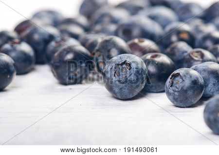 Fresh blueberries with mint on a wooden white table. Natural antioxidant. Concept of healthy food. Organic superfood