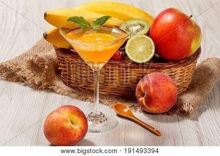 Orange Jelly In The Glass, Fresh Strawberries, Nectarine, Lime, Kiwi, Banana, Apple In A Wicker Bask