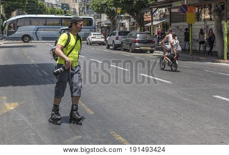 Tel Aviv, Israel - June 2017: street photographer at rollerblades
