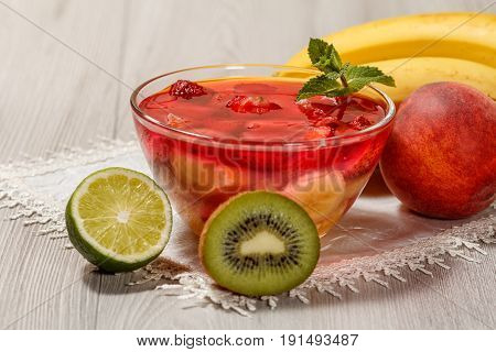 Cherry Jelly With Strawberry Pieces In The Glass Bowl Topped Mint Leaves And Fruits On The White Nap
