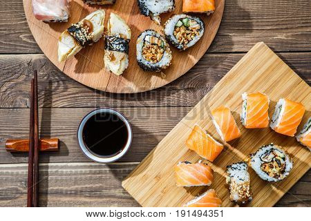 Two sets of rolls on wooden plates on table with soy sauce and chopsticks