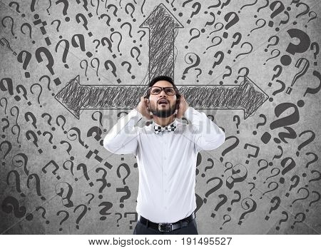 Shocked businessman with arrow symbols and question marks on wall