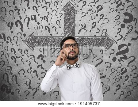 Confused businessman in front of wall with arrow directions and question marks