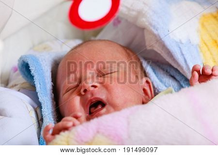 Infant care teething pain colic ache concept. Little newborn baby crying in bed surrounded with blankets