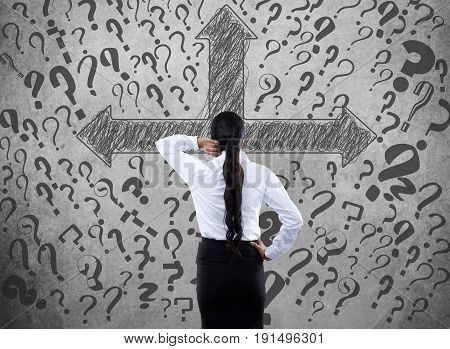 Confused businesswoman looking at arrow directional signs and question marks