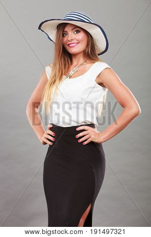 Fashionable style clothes good looking concept. Woman with brown hair wearing long black white dress and sun hat.