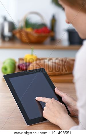 Close-up of four human hands are gesticulate over a tablet in the kitchen. Friends having fun while choosing menu or making online shopping. So much ideas for tasty cooking. Vegetarian, healthy meal and friendship concept