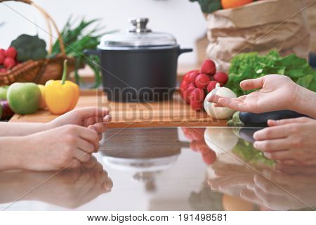 Close-up of four human hands are gesticulate over a table in the kitchen. Friends having fun while choosing menu or making online shopping. So much ideas for tasty cooking. Vegetarian, healthy meal and friendship concept