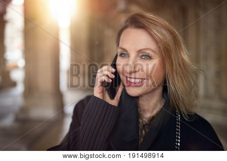 Attractive woman talking on a smartphone inside a large building smiling with pleasure as she listens to the conversation