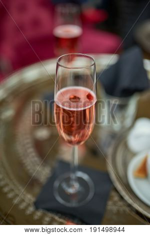 Flute of romantic sparkling rose champagne on a table in a restaurant viewed close up high angle with focus to the beverage