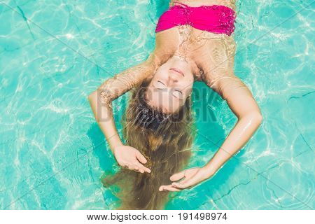 Beautiful Young Woman Floating In Pool Relaxing Top View. Holiday Concept