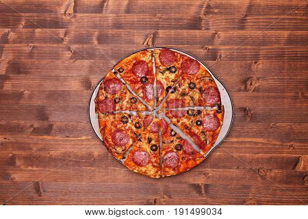 Sliced pizza on baking pan - top view on brown wooden desk with copy space