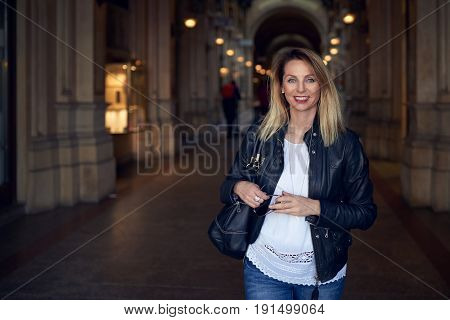 Attractive trendy young woman walking through an arcade with her handbag over her shoulder smiling happily at the camera with copy space