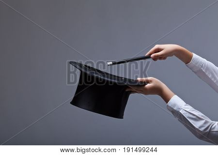 Magic hat and wand in child hands - against grey background with copy space