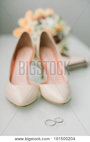 gatherings of the bride on a wedding. Wedding rings from white gold, elegant beige shoes and a wedding bouquet from fresh flowers on a light background. wedding, passionate love concept.